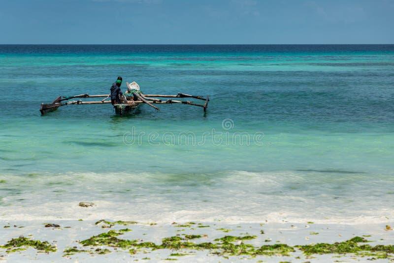 单桅三角帆船小船的渔夫在桑给巴尔 免版税库存照片
