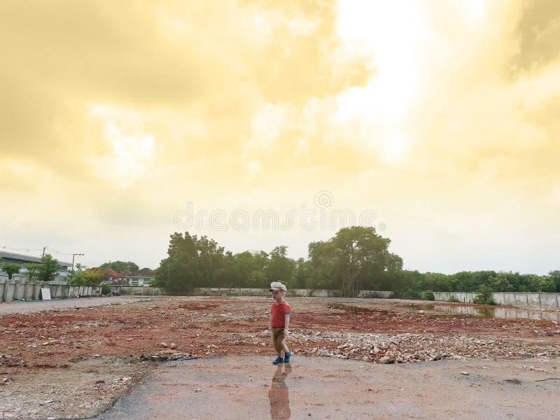 单独亚洲男孩立场在日落时间的爆破荒原建筑区域与raylight和多云 库存照片