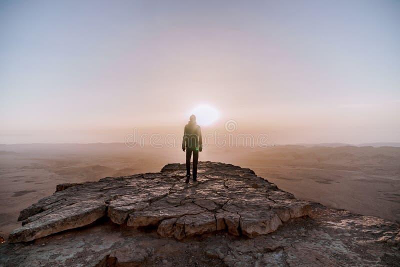 单独人在以色列Neqev沙漠敬佩日出看法  年轻男性收养站立在峭壁边缘 免版税库存照片