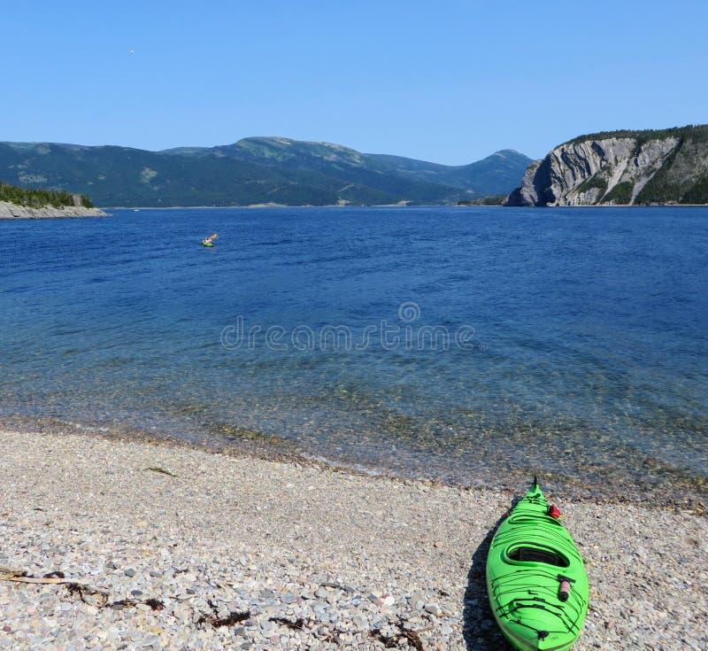 单独休息沿在Bonne海湾的美丽的水的一艘唯一绿色皮船,在格罗莫讷国家公园,纽芬兰 免版税图库摄影