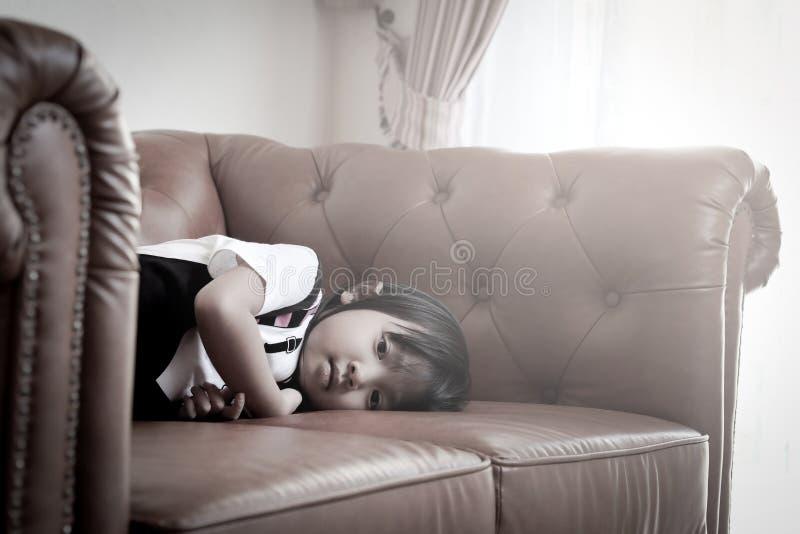 单独偏僻的哀伤的心情的亚裔女孩在长沙发 免版税库存图片