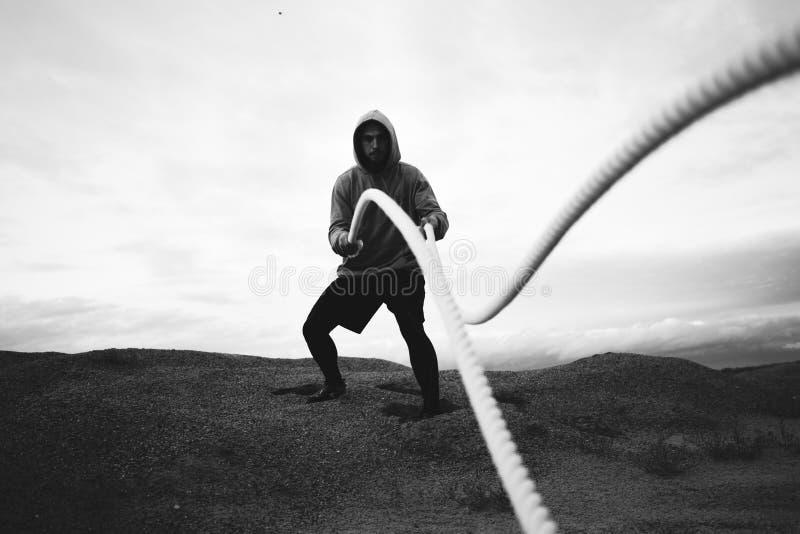 单独做健身锻炼的体育人在海滩 黑白颜色 免版税图库摄影