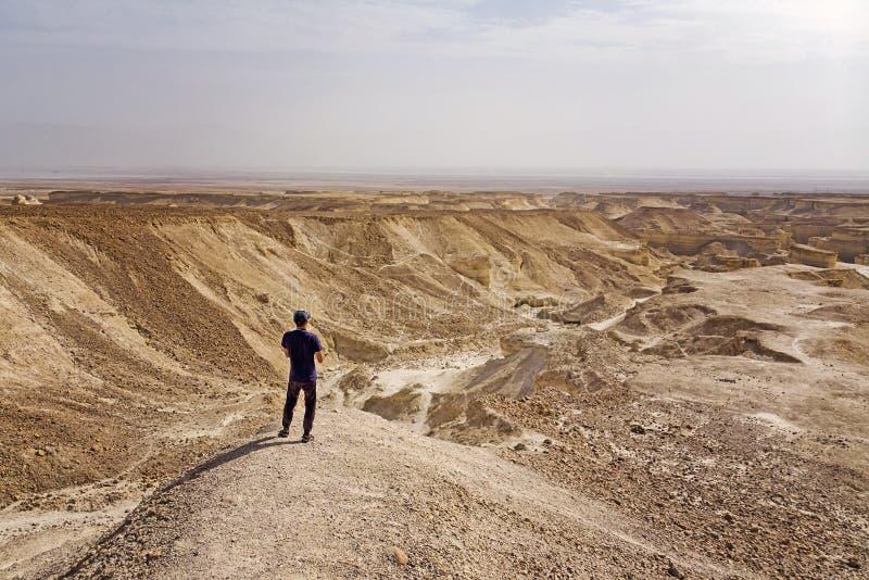 单独停留在沙漠和朝前看对天际的棒球帽的年轻白种人人 年轻旅行家发现无生命 免版税库存照片