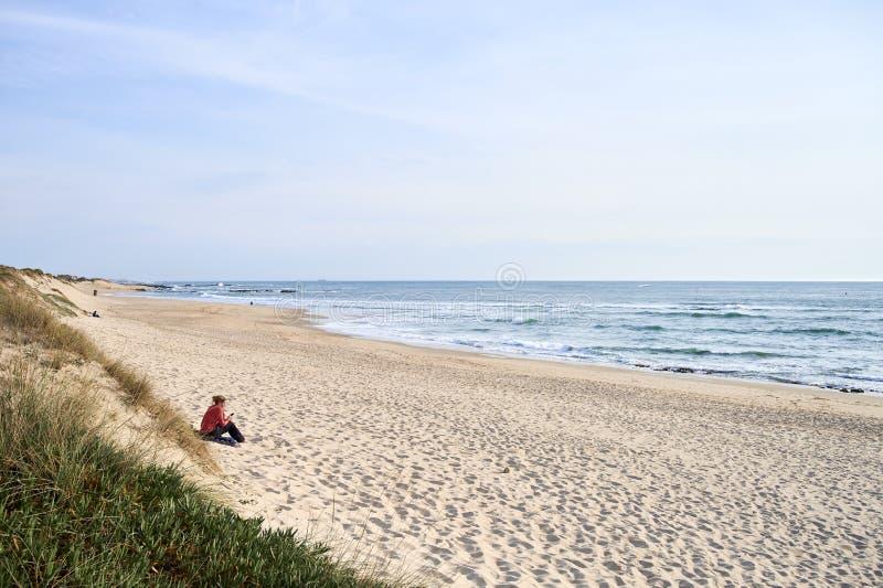 单独发短信在海滩的妇女 免版税库存照片