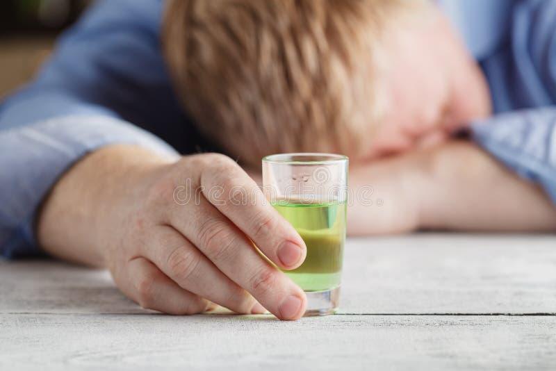 单独和喝在他自己的年轻人感觉许多酒精 免版税库存图片