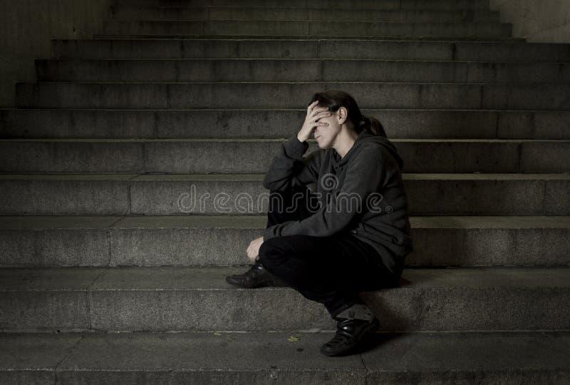 单独哀伤的妇女看起来街道地铁楼梯遭受的消沉的看病和无能为力 免版税图库摄影
