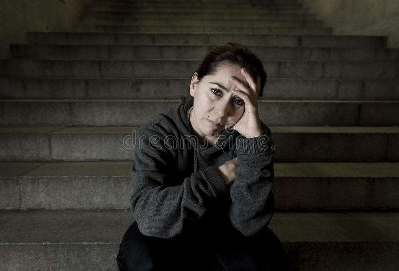 单独哀伤的妇女看起来街道地铁楼梯遭受的消沉的看病和无能为力 免版税库存图片