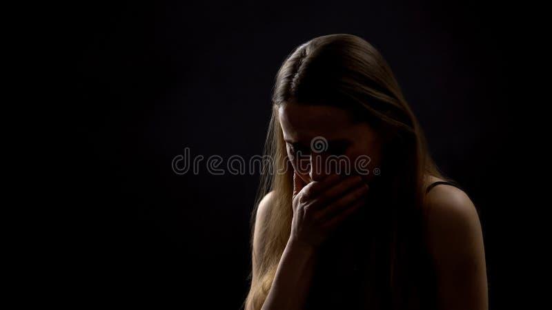 单独坐反对黑暗的背景的哭泣的夫人,遭受生活问题 图库摄影