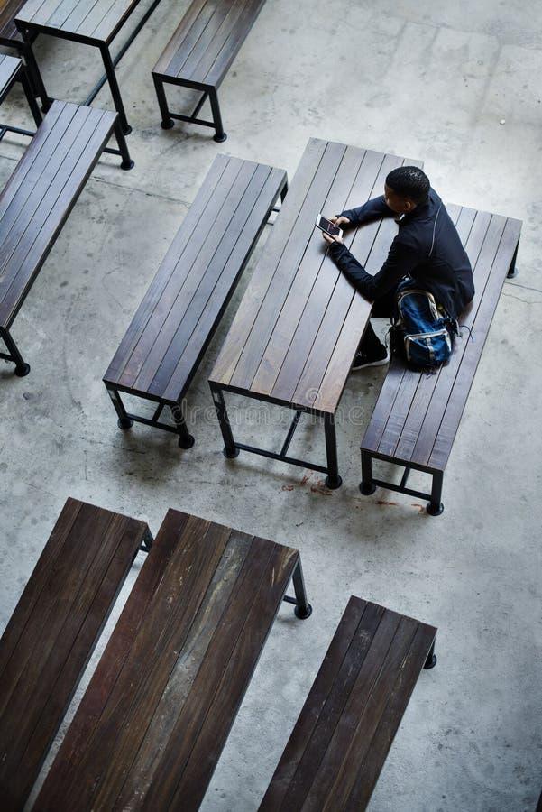 单独坐在一套空的军用餐具的十几岁的男孩 免版税库存图片