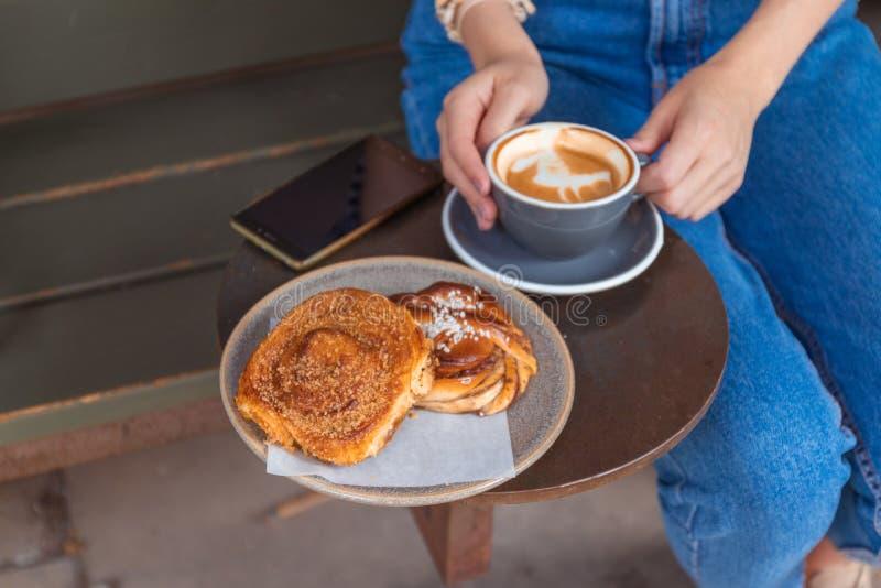 单独坐在与一杯咖啡的一个咖啡馆的年轻迷人的妇女,当放松在咖啡馆时 免版税图库摄影