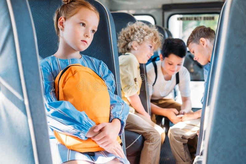 单独坐在学校班车的沮丧的小女小学生,当获得她的同学乐趣一起时 库存照片