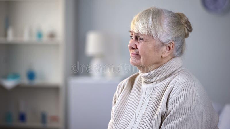 单独坐在客厅的沮丧的资深妇女,放弃由亲戚 免版税库存照片