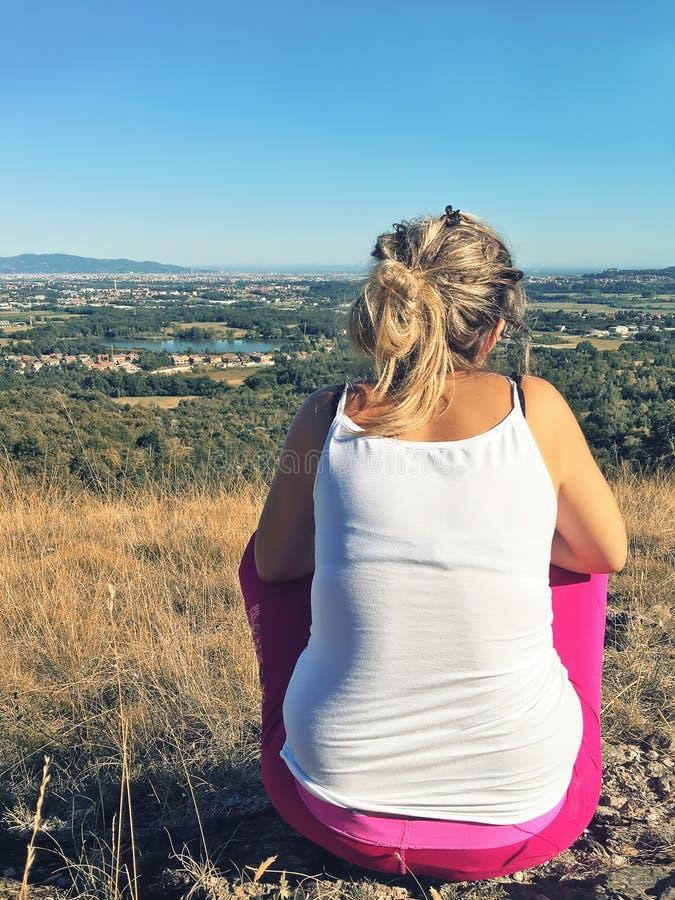 单独坐在山的女孩赛跑者 免版税库存图片