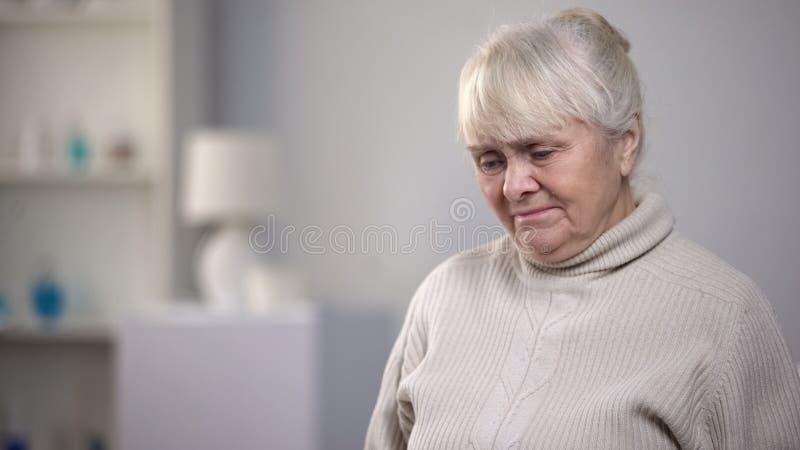 单独坐在康复中心的哭泣的老妇人,遭受病症 图库摄影