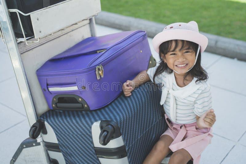 单独坐在手提箱旁边的女孩在机场 免版税图库摄影