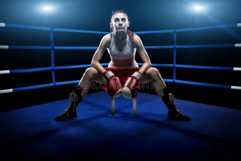 单独坐在拳击场的拳击妇女,包围由蓝色光 免版税库存照片