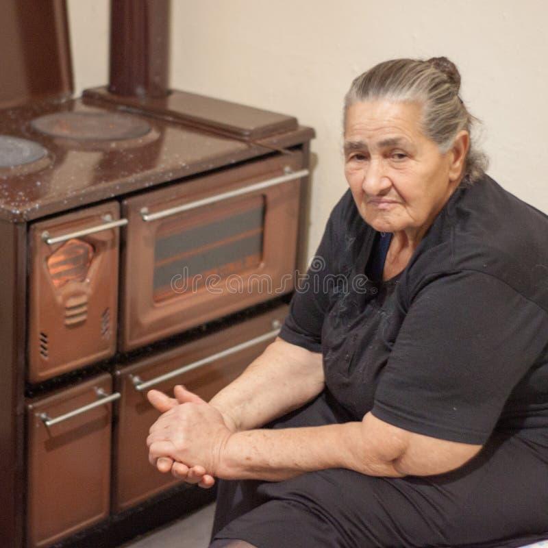 单独坐在木加热器旁边的老妇人 库存照片
