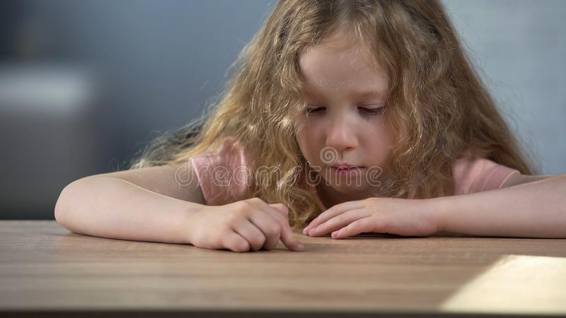 单独坐在桌上和作梦关于妹的孤独的白种人女孩 库存照片