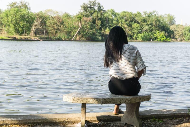单独坐在河的椅子的亚裔妇女 桥梁和湖背景 免版税库存照片