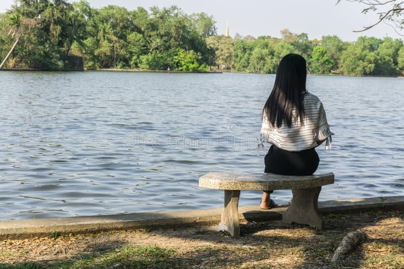 单独坐在河的椅子的亚裔妇女 桥梁和湖背景 库存图片