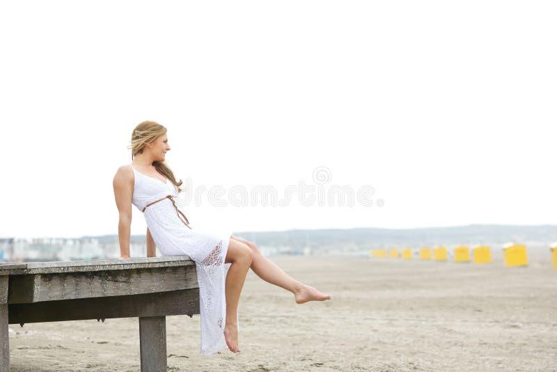单独坐在海滩的少妇 免版税库存照片