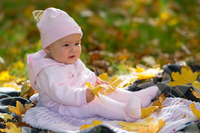 单独坐在秋天叶子的桃红色衣物的婴孩 免版税库存照片