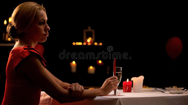 单独坐在餐馆,男朋友的不快乐的花姑娘晚为晚餐 免版税库存照片