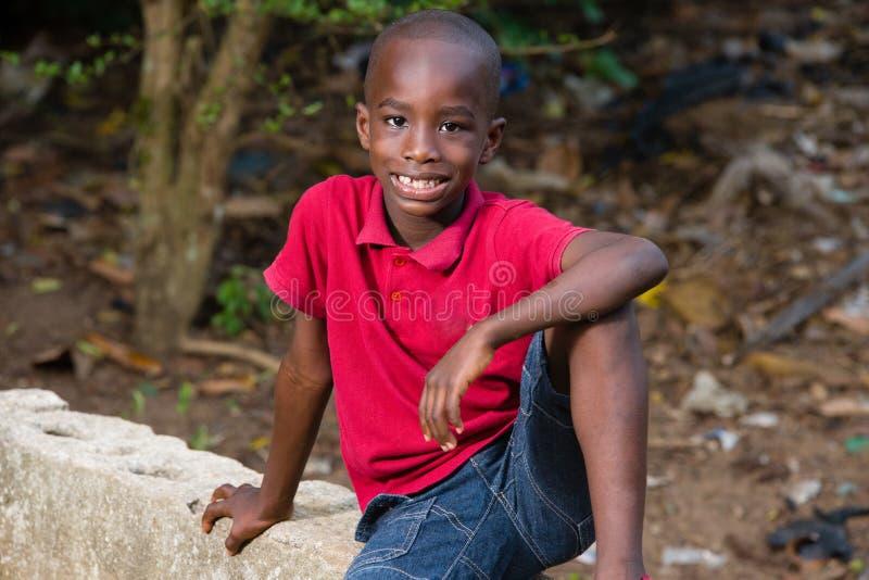 单独坐愉快的小男孩外面 免版税库存图片