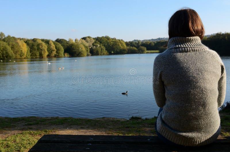 单独坐由湖的一件温暖的套头衫的妇女 免版税库存照片