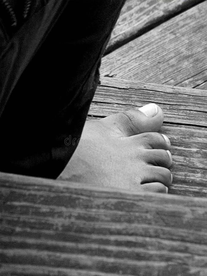 单独坐的裤子和的脚 免版税库存图片