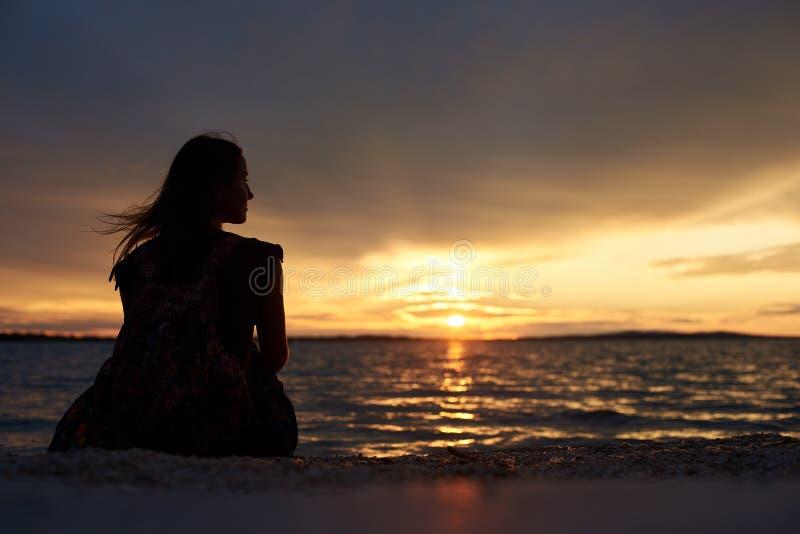 单独妇女剪影水边缘的,享受美好的海景在日落 免版税库存图片
