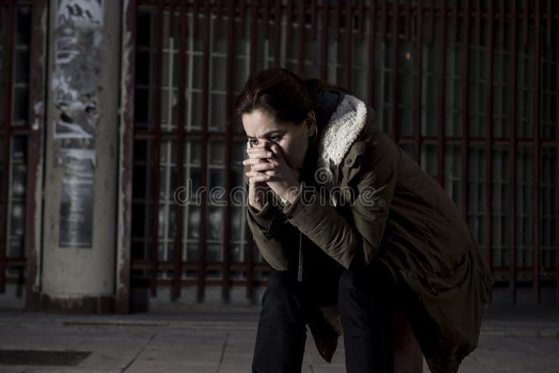 单独妇女看起来哀伤的绝望和无能为力的开会的街道遭受的消沉的偏僻在肮脏的黑暗的都市背景中 库存照片
