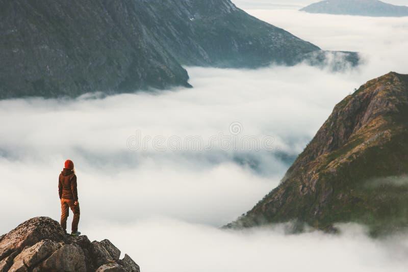 单独峭壁俯视的山云彩的旅客 免版税图库摄影