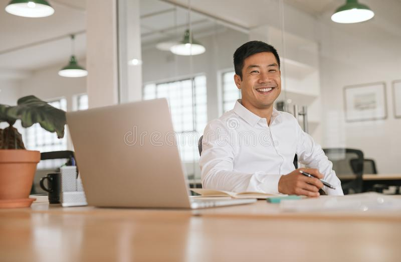 单独工作在他的办公桌的微笑的年轻亚洲商人 库存照片