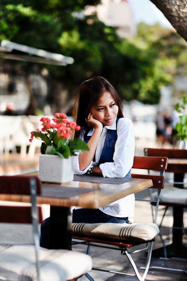 单独年轻美丽的亚裔妇女画象等待的咖啡馆的和天作梦 免版税图库摄影