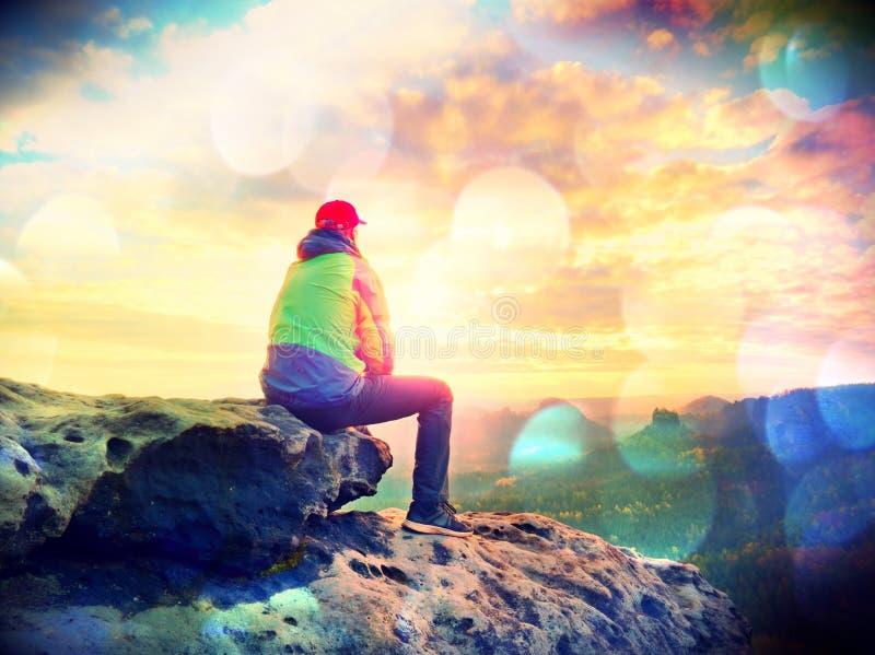 单独旅游采取绿色黑夹克的休息远足者坐岩石峰顶,当享受看法时 库存照片