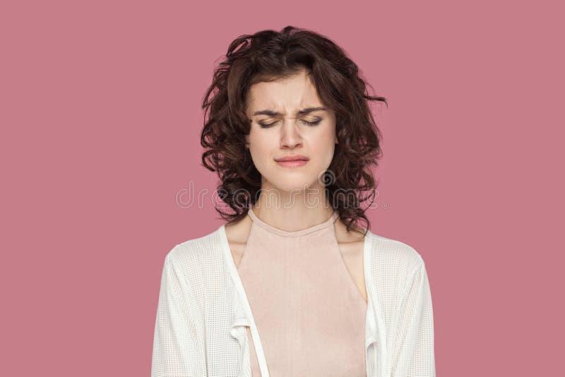 单独有卷曲发型的哀伤的沮丧的美丽的深色的年轻女人特写镜头画象在站立与闭合的便装样式 免版税库存图片