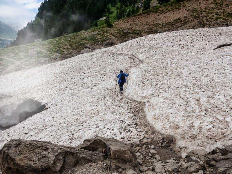 单独有警棒的勇敢的妇女远足的十字架在山的冰川 免版税库存照片