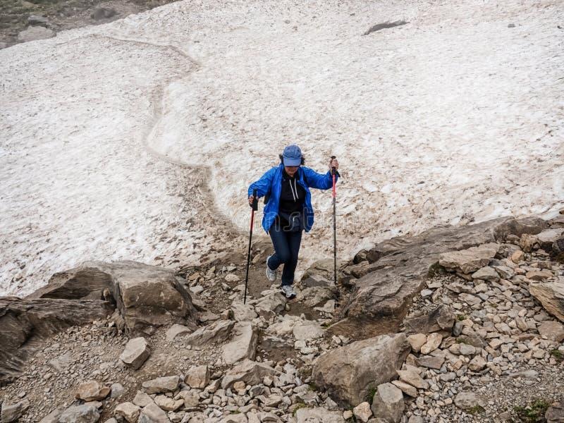 单独有警棒的勇敢的妇女远足的十字架在山的冰川 免版税库存图片