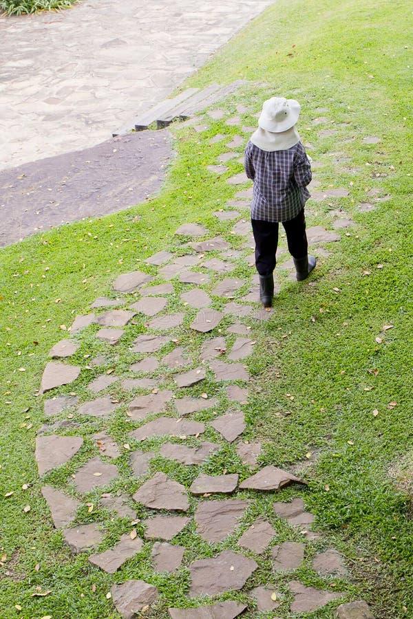单独果树栽培者步行在方式砖在公园里 免版税库存图片