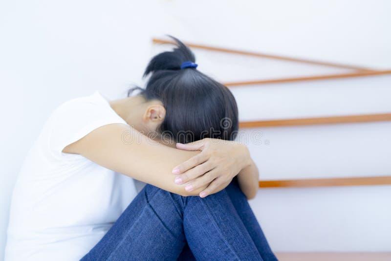 单独消沉妇女坐她看非常注重的楼梯 消沉的概念 库存照片