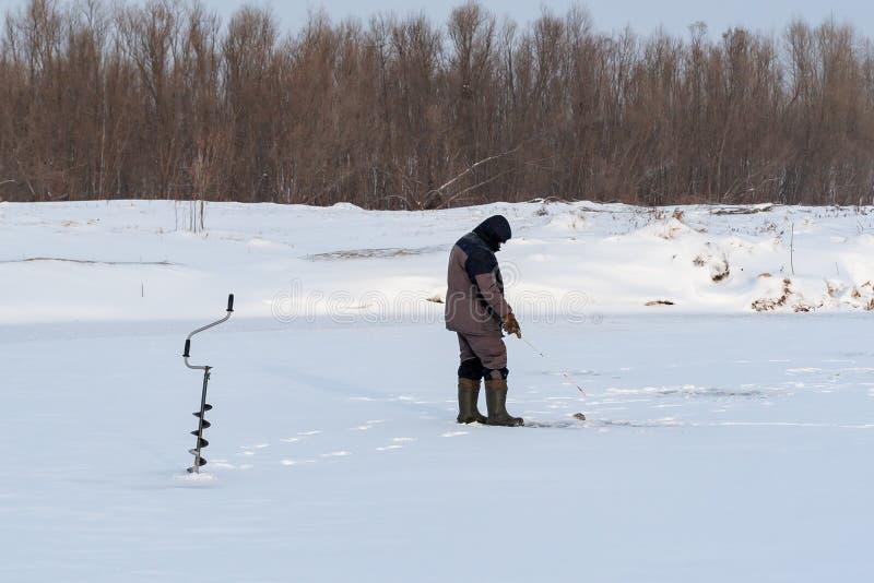 单独渔夫在一个冬天抓在冰,冷淡的天的鱼 免版税库存图片