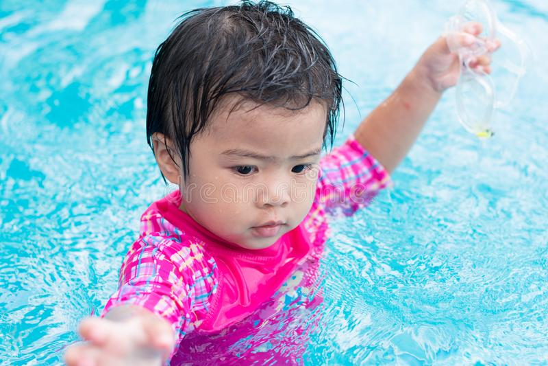 单独游泳在游泳池的小的亚洲女孩尝试,室外 免版税库存图片