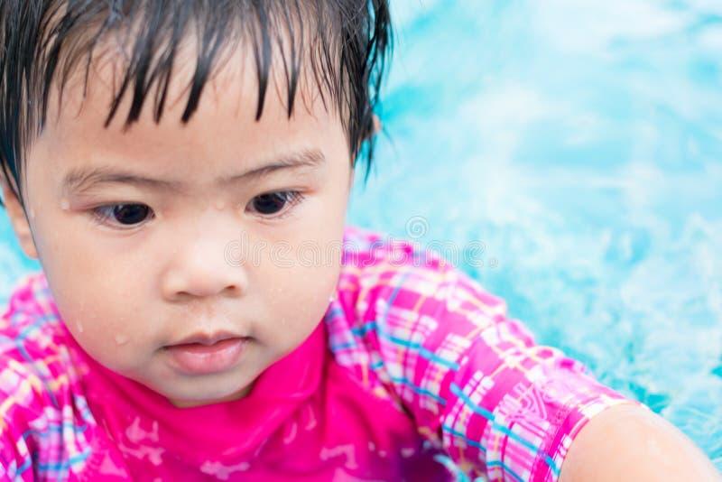 单独游泳在游泳池的小的亚洲女孩尝试 免版税库存照片
