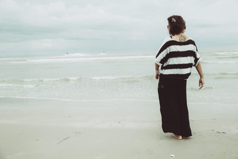 单独画象亚裔单身纹身花刺行家indy妇女偏僻的立场在海滩 免版税库存图片
