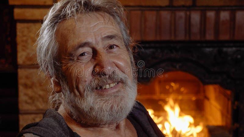 单独画象老人在家在壁炉附近 库存照片