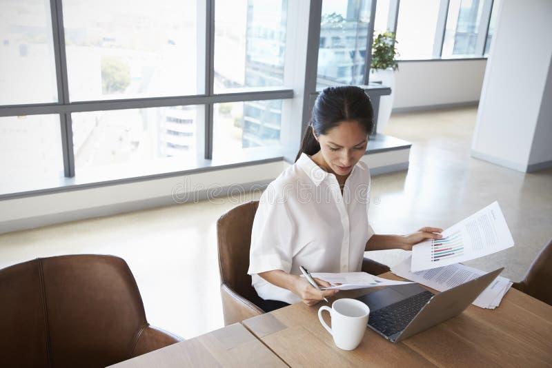 单独研究膝上型计算机的女实业家在办公室会议室里 库存图片