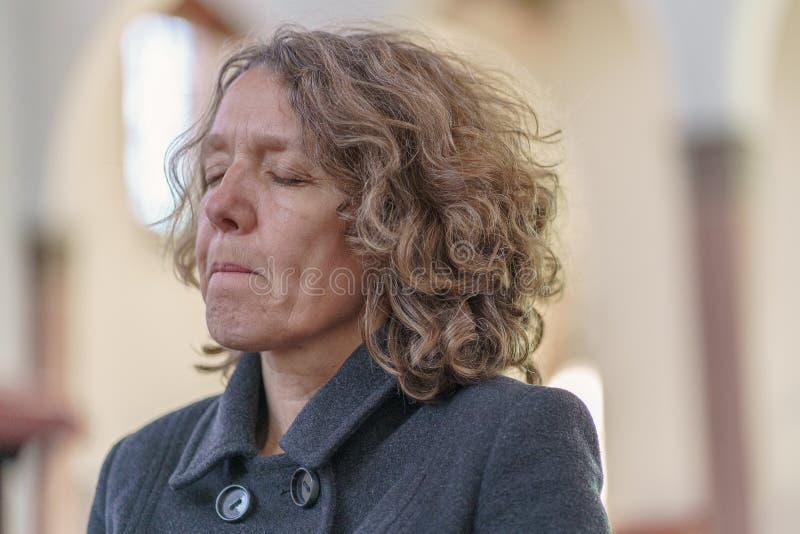 单独祈祷在教会里的宗教虔诚的妇女 图库摄影