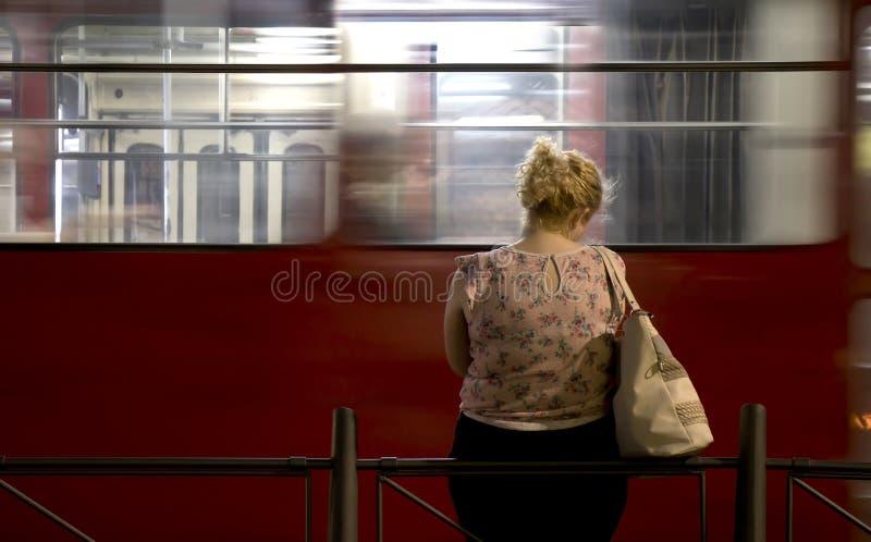 单独站立在一个公共汽车站的一名年轻白肤金发的妇女夜 库存照片