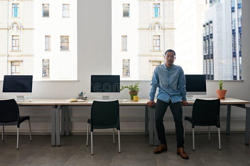 单独站立在一个现代办公室的年轻亚裔设计师 免版税图库摄影